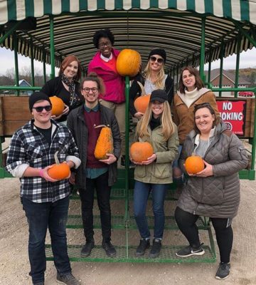 Team at the pumpkin farm holding pumpkins
